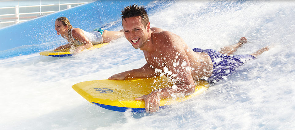 Couple on skim boards in Royal Caribbean surf simulator FlowRider